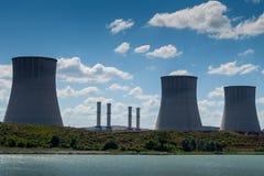 I camini termici della centrale elettrica si avvicinano al lago fotografia stock