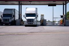 I camion dei semi sono alla stazione di servizio per rifornire di carburante immagini stock