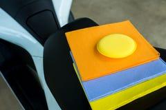 I camosci dei tergicristalli molti colorano il panno e la cera gialla della spugna con l'automobile bianca Fotografia Stock Libera da Diritti