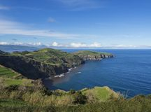 I campi verdi pascolano e scogliere costiere ed orizzonte blu del cielo e dell'oceano alla costa del nord dell'isola di Miguel de fotografie stock libere da diritti