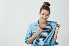 I can borrow you my shirt. Indoor portrait of cool attractive european female with bun hairstyle, taking off denim. Clothes while smiling with intrigued and stock photos