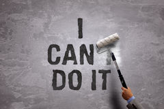 I can do it. Changing the word can't to can by painting over and erasing part of it with a paint roller on a concrete wall in the phrase i can do it