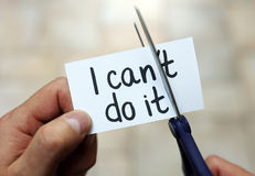 I can do it. Man using scissors to remove the word can't to read I can do it concept for self belief, positive attitude and motivation