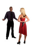 I Can Explain. Man in shirt and tie desperately trying to explain himself to a blond woman in a red dress holding a pistol behind her back stock photos