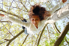 I can fly. A girl swinging upside down from a tree Stock Image