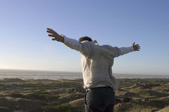 I can fly. Youth on hilltop with open arms. Ocean in background stock image