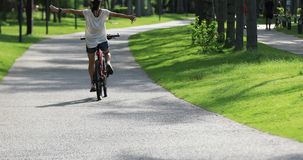 I can fly with my bike. Happy young woman riding bike at tropical park with arms open stock video