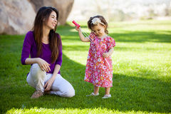 I can make some bubbles mom. Pretty baby girl and her young mom trying to make some bubbles at the park Royalty Free Stock Images