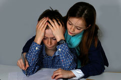 I can not do my homework. Weeping  teenager boy sitting at his desk  , trying to do  his maths school  homework. He gets help from his sister Stock Image