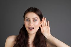 I can not hear you. Beautiful young positive girl with long brunette hair with a hand near the ear royalty free stock photo