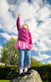 I can reach the sky. Sweet girl reaching the sky with hand and flowers Royalty Free Stock Image