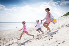 I can see the sea!. Young single parent family running down the sanddunes at the beach Stock Photo