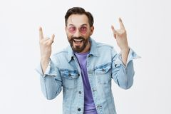 I can still party and rock. Funny handsome adult male in trendy sunglasses and stylish denim jacket showing heavy metal. Sign and smiling joyfully, remembering Royalty Free Stock Photo