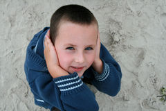 I can't hear you. 5 years old boy on the beach, closed his ears with hands Royalty Free Stock Photography