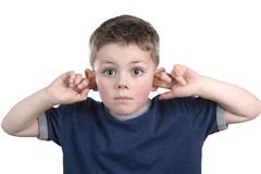 I can't hear you. Young boy with his fingers in his ears so he can not hear Stock Photography