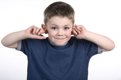 I can't hear you. Young boy with his fingers in his ears so he can not hear Stock Photos