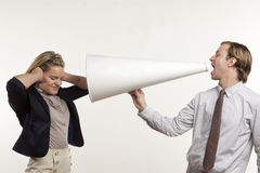 I can't hear you. Business man yelling through megaphone at business woman Royalty Free Stock Photography