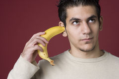 I can't hear you I have a bananna in my ear. Man listens to his inner bananna in a studio portrait Royalty Free Stock Images