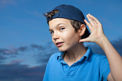 I can't hear you!. Teenage boy, standing outside, its evening, his making a sign with his left hand as if he cannot hear properly Stock Images