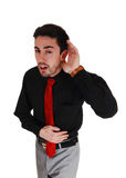 I can't hear you!. A young businessman holding his hand behind his ear, he can not hear Royalty Free Stock Photos