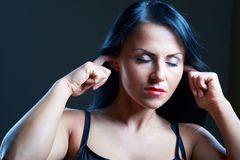 I Can't Hear You. Young woman covering her ears Royalty Free Stock Images