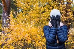 I can't look at autumn. Girl stands near yellow autumn bush and refuses to believe in the end of summer Stock Image