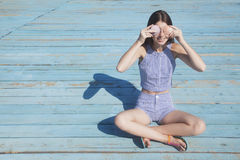 I can't see you!. Attractive teenager girl sitting on the beach and closes her eyes by the seashells Stock Images