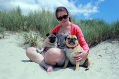 I cani ed il proprietario del carlino su una spiaggia soleggiata abbelliscono Fotografia Stock Libera da Diritti