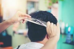 I capelli asiatici di taglio dell'uomo al barbiere fotografie stock libere da diritti