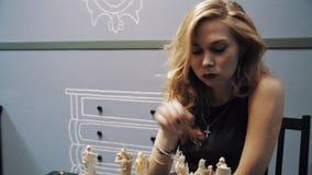 I capelli attraenti biondi di carezza della donna davanti alla tavola di scacchi, si allontanano stock footage