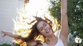 I capelli d'ondeggiamento di risata positivi della ragazza e girano nell'accensione solare luminosa all'aperto archivi video