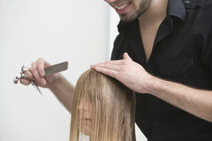 I capelli del cliente della regolazione del parrucchiere prima di taglio di capelli al salone fotografia stock