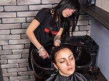 I capelli femminili attraenti di lavaggio del parrucchiere della giovane donna dentro erano Fotografia Stock