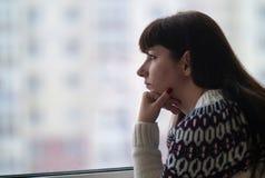 I capelli lunghi della donna guardano meditatamente il primo piano della finestra, contro lo sfondo delle case immagine stock libera da diritti