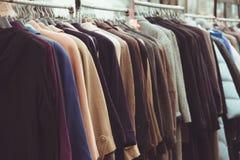 I cappotti dell'inverno del fuoco selettivo hanno appeso su uno scaffale dei vestiti Immagini Stock