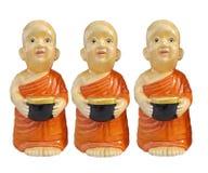 I caratteri buddisti della resina del principiante che tengono le elemosine lanciano a disposizione isolato su fondo bianco immagine stock