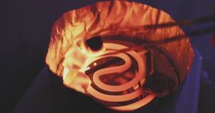 I carboni della noce di cocco per un narghilé sono fritti su un piatto a spirale e poi una mano con le tenaglie del metallo le fa video d archivio