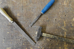 I carpentieri anziani martellano la raspa e lo scalpello sul backgrou di legno d'annata Immagine Stock