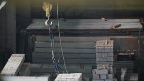 I cavi del metallo sul gancio sono fissi per l'operazione del blocco in calcestruzzo sulla fabbricazione stock footage