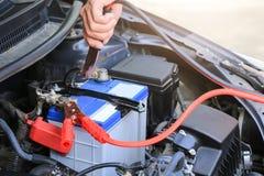 I cavi del saltatore della batteria di usi del meccanico di automobile caricano una batteria morta Immagine Stock