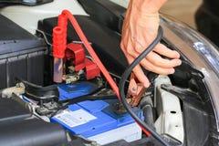 I cavi del saltatore della batteria di usi del meccanico di automobile caricano una batteria morta Immagine Stock Libera da Diritti