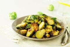 I cavoletti di Bruxelles hanno arrostito fritto con le cipolle su una vista superiore del piatto immagini stock