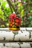 I ceppi della betulla ed il vaso di legno decorativo in Khokhloma disegnano, riempito troppo dai mazzi di ribes maturo Fotografie Stock