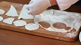 I cerchi tagliati dalla pasta cruda del biscotto hanno rotolato la cucitura su un bordo di legno stock footage