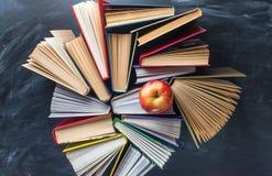 I certi libri e mela rossa sullo scrittorio sopra la lavagna immagine stock