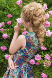 I cespugli di rose di fioritura vicini della bella ragazza sexy delicata adorabile di estate riscaldano il giorno con bei capelli Immagine Stock