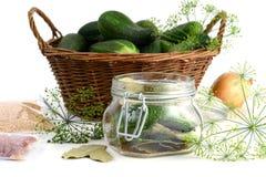 I cetrioli casalinghi in vetro del barattolo con le erbe gradiscono l'aneto e le cipolle Immagine Stock Libera da Diritti