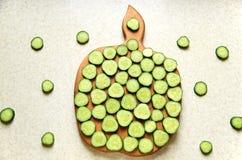 I cetrioli crudi su una mela di legno di taglio imbarcano Fotografia Stock