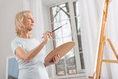 Creative mature woman estimating drawing. I change this. Glad appealing mature woman staring at easel while posing in profile and rising tassel stock photography