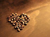 I chicchi di caffè alla prima colazione hanno modellato nel cuore sul fondo di legno del grano fotografia stock libera da diritti